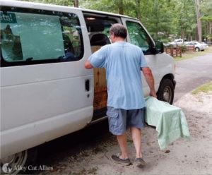 A man places a humane box trap in a van